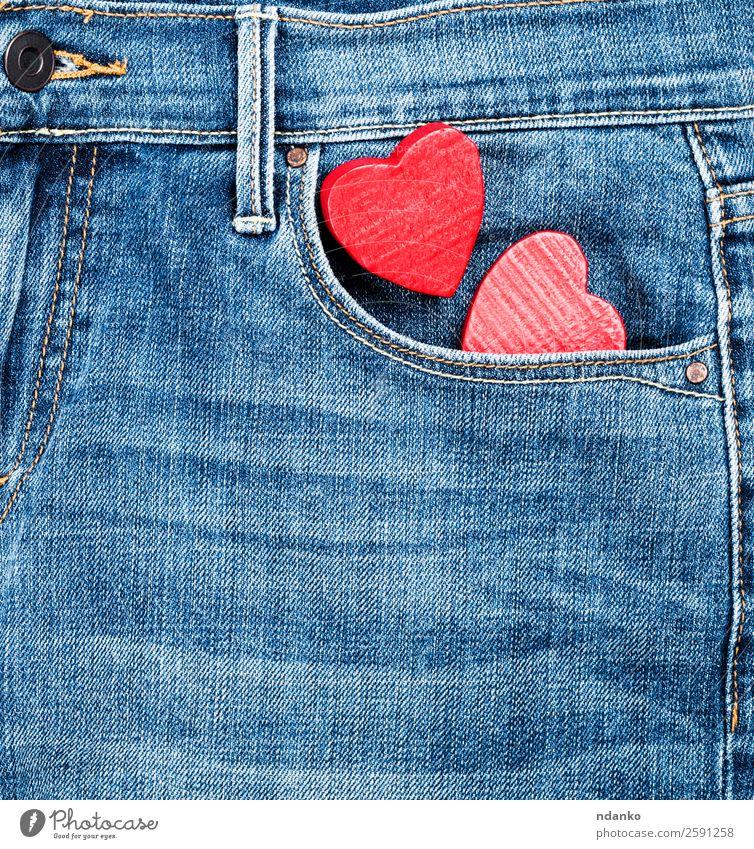 Jeans und zwei rote Holzherzen Stil Valentinstag Mode Bekleidung Hose Jeanshose Stoff Herz Liebe blau Farbe Tradition Hintergrund Leinwand lässig Baumwolle