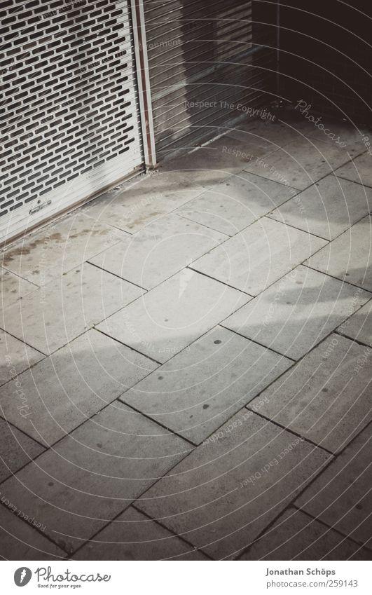 Straßenrand Stadt Haus Wand grau Gebäude geschlossen leer Perspektive trist einfach Stadtleben Bürgersteig Tor Stadtzentrum Neigung