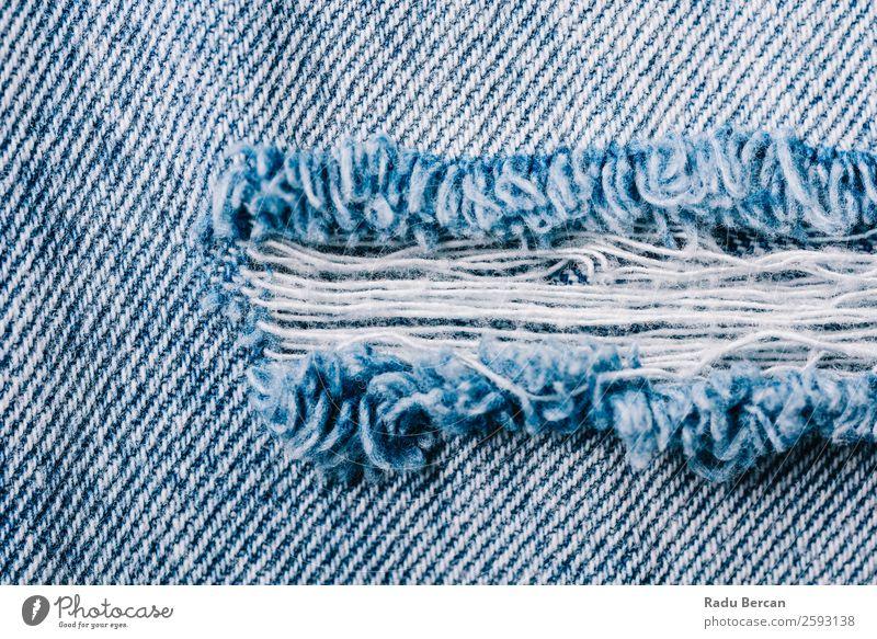 Denim Textur von zerrissenen Jeans Jeanshose gerissen Konsistenz Jeansstoff Hintergrundbild Stoff blau Muster Design lässig Textil Material alt Nahaufnahme Mode