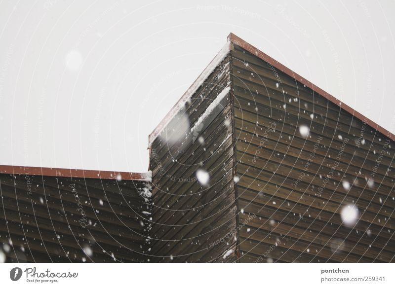 Schneefall im Winter. Schneeflocken und hausfassade mit Holzverkleidung schlechtes Wetter Haus Dach kalt trist Dachschräge Farbfoto Gedeckte Farben