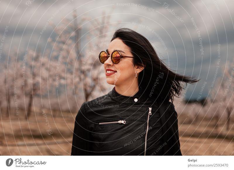 Hübsches brünettes Mädchen Stil Glück schön Gesicht Garten Mensch Frau Erwachsene Natur Baum Blume Blüte Park Mode Jacke Leder Sonnenbrille Lächeln Fröhlichkeit