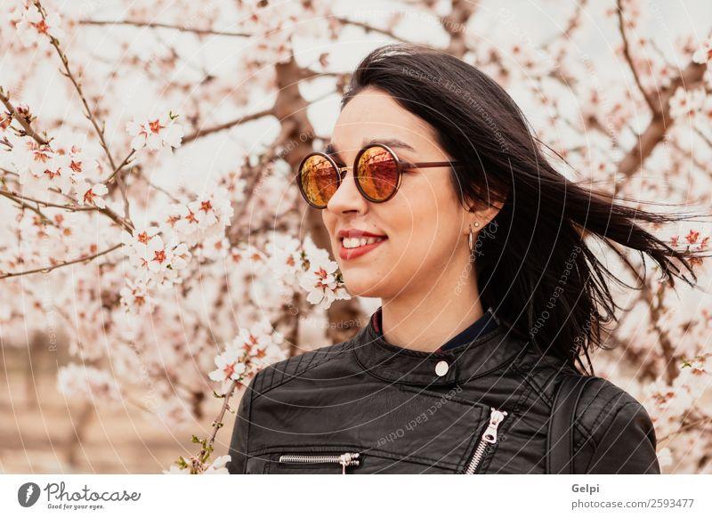 Brünettes Mädchen Stil Glück schön Gesicht Garten Mensch Frau Erwachsene Natur Baum Blume Blüte Park Mode Jacke Leder Sonnenbrille brünett Lächeln Fröhlichkeit