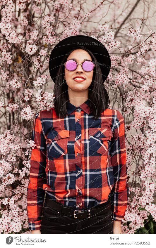 Hübsches brünettes Mädchen Stil Glück schön Gesicht Garten Mensch Frau Erwachsene Natur Baum Blume Blüte Park Mode Sonnenbrille Hut Lächeln Fröhlichkeit frisch