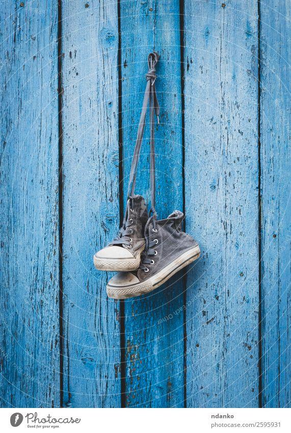 alte getragene schwarze Textilsneakers Stil Sport Mode Bekleidung Schuhe Turnschuh Holz Fitness trendy retro blau weiß erhängen Schuhbänder altehrwürdig jung