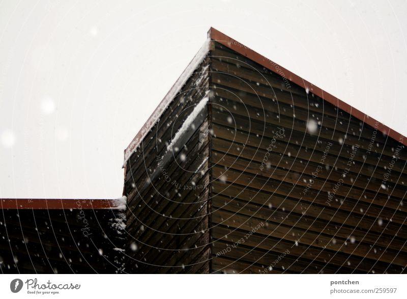 Grauer Wintertag. Schneeflocken und hausfassade. Holzverkleidung Wetter schlechtes Wetter Schneefall Haus Einfamilienhaus Dach braun grau rot weiß Farbfoto