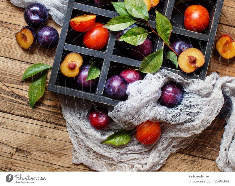 Frische Pflaumen mit Blättern Frucht Ernährung Vegetarische Ernährung Diät Sommer Tisch Herbst Blatt Holz frisch saftig braun purpur roh reif Ackerbau süß
