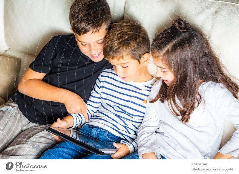 Drei Kinder benutzen zu Hause ein Tablett. Lifestyle Freude Glück schön Freizeit & Hobby Spielen lesen Sofa Handy Spielkonsole Computer Notebook Bildschirm