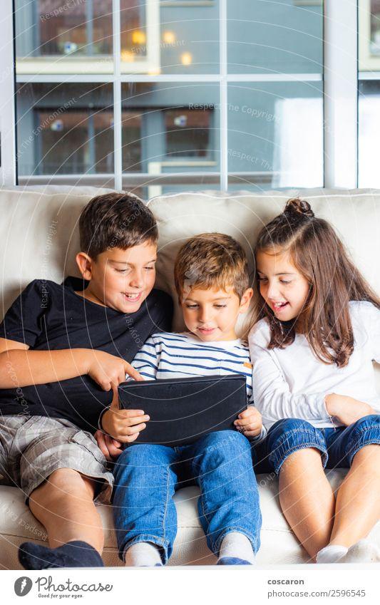 Drei Kinder benutzen zu Hause ein Tablett. Lifestyle Freude Glück schön Freizeit & Hobby Spielen Sofa Bildung lernen Schüler Handy Computer Notebook Bildschirm