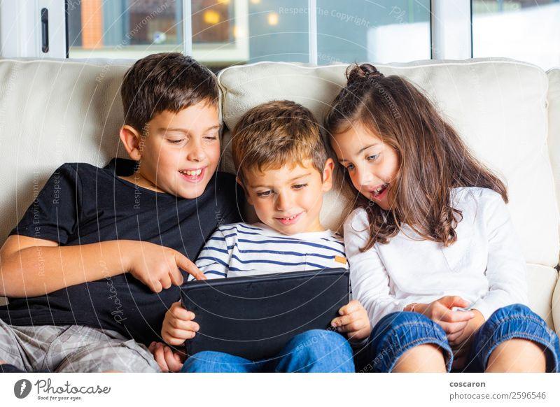 Drei Kinder benutzen zu Hause ein Tablett. Lifestyle Freude Glück schön Freizeit & Hobby Spielen Sofa Bildung lernen Handy Computer Notebook Bildschirm
