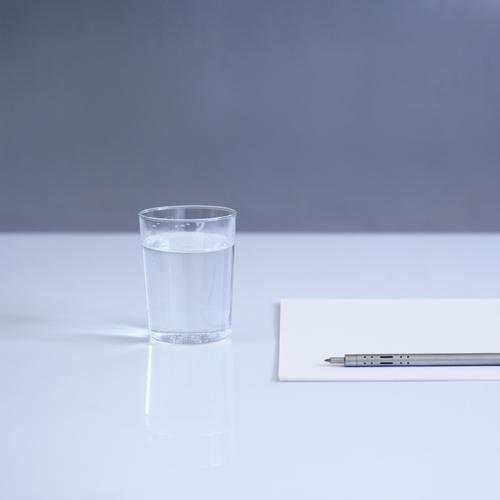 blank Getränk Erfrischungsgetränk Trinkwasser Glas Schreibwaren Papier Schreibstift ästhetisch einfach kalt modern blau grau weiß Tisch Farbfoto Innenaufnahme