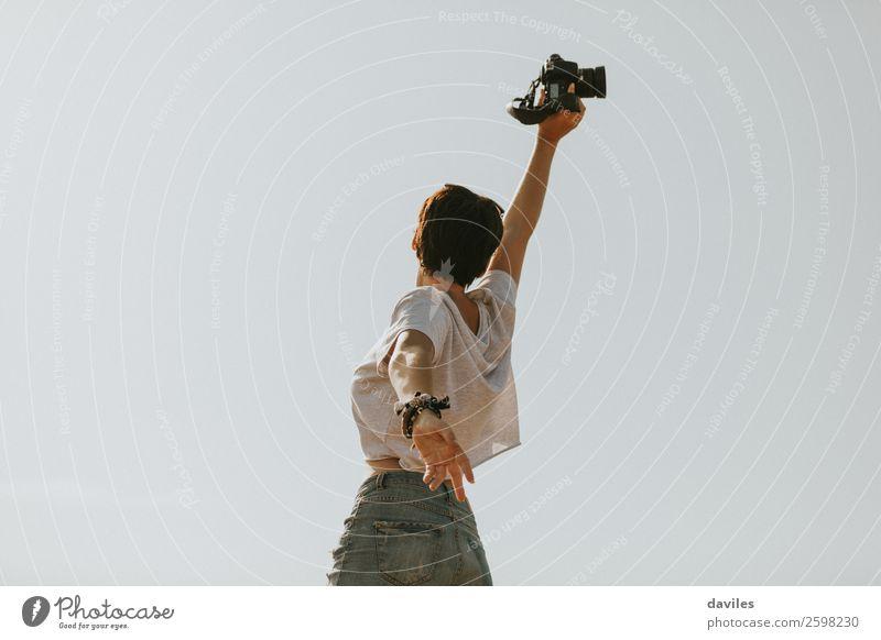 Junges Mädchen, das mit einer Kamera im Freien springt. Lifestyle Freude Glück Körper Freiheit Sommer Berge u. Gebirge Fotokamera Mensch feminin Junge Frau