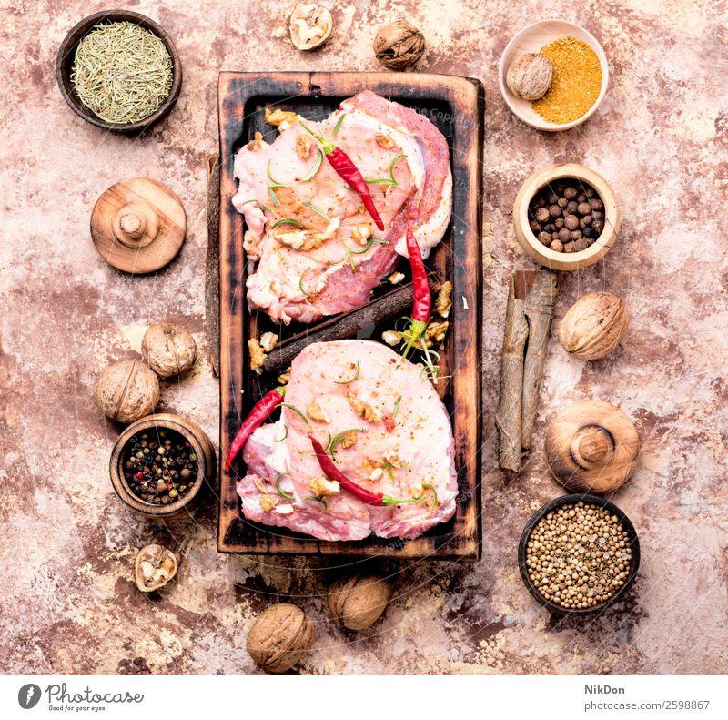 Rohes Fleisch, Schweinesteak roh Lebensmittel Filet Schweinefleisch Steak rot frisch ungekocht Bestandteil geschnitten Walnussholz Paprika Rosmarin hacken