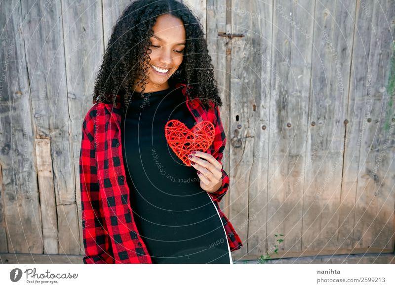 Schöne junge Frau, die ein rotes Herz hält. Lifestyle Stil Freude Haare & Frisuren Leben Mensch feminin Junge Frau Jugendliche Erwachsene