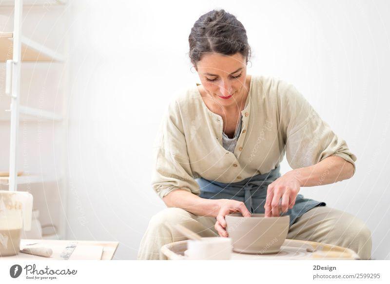 Junge Frau sitzt am Tisch und stellt Ton oder Keramik her. Geschirr Freizeit & Hobby Handarbeit Arbeit & Erwerbstätigkeit Beruf Handwerker Arbeitsplatz Büro