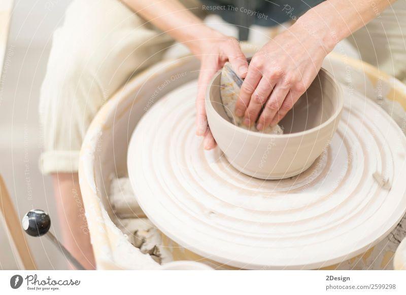 Junge Frau sitzt am Tisch und stellt Ton oder Keramik her. Geschirr Freizeit & Hobby Handarbeit Arbeit & Erwerbstätigkeit Beruf Arbeitsplatz Büro Handwerk