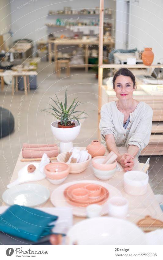 Frau in Arbeitskleidung in ihrer Werkstatt am Tisch mit handgefertigten Gegenständen Geschirr Freizeit & Hobby Handarbeit Arbeit & Erwerbstätigkeit Beruf