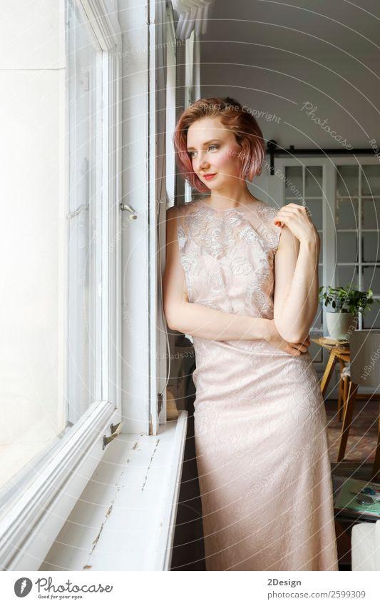 junge schöne Dame, die im Wohnzimmer neben einem Fenster posiert. Reichtum elegant Stil Glück Körper Erholung Möbel Mensch feminin Junge Frau Jugendliche
