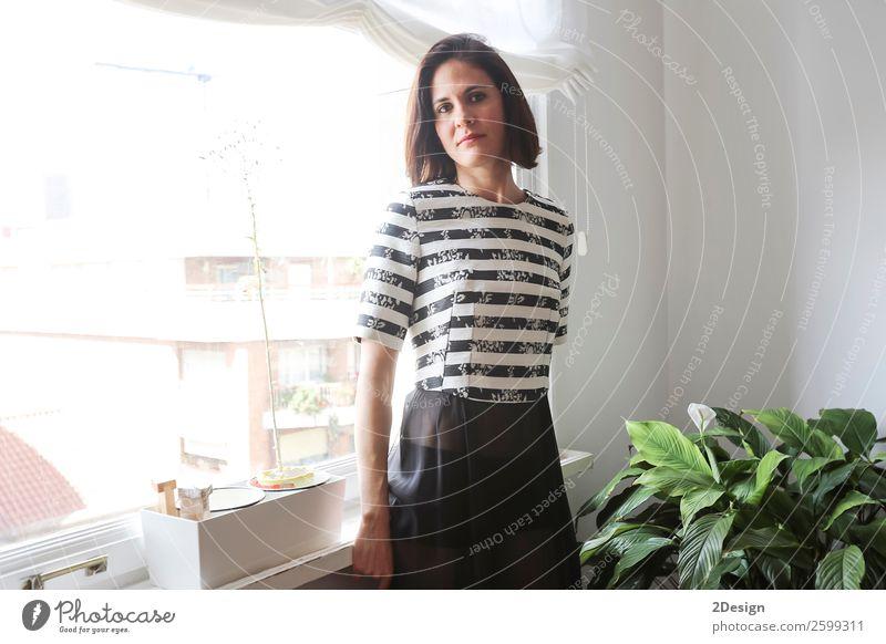 junge schöne Dame, die im Wohnzimmer neben einem Fenster posiert. Reichtum elegant Stil Glück Körper Erholung Möbel Mensch Frau Erwachsene Mode Kleid warten