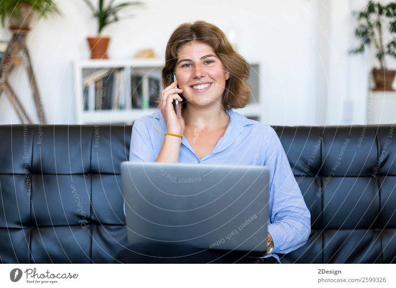Unternehmerin im blauen Hemd bei der Arbeit mit einem Laptop, die zu Hause auf einer Couch sitzt kaufen Glück schön Sofa Schule lernen Studium