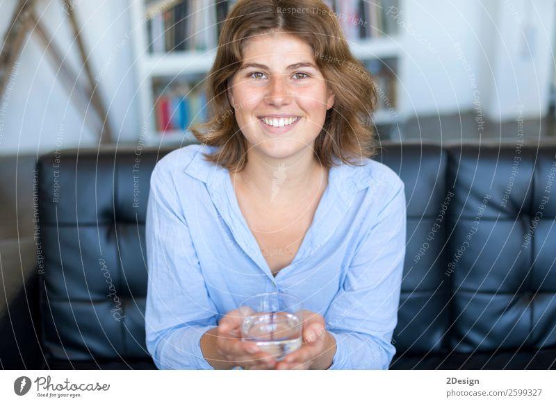 Frontalansicht Porträt eines glücklichen Teenagers mit einem Glas Wasser. Diät Getränk trinken Lifestyle Glück schön Gesicht Wellness Leben Sofa Fotokamera