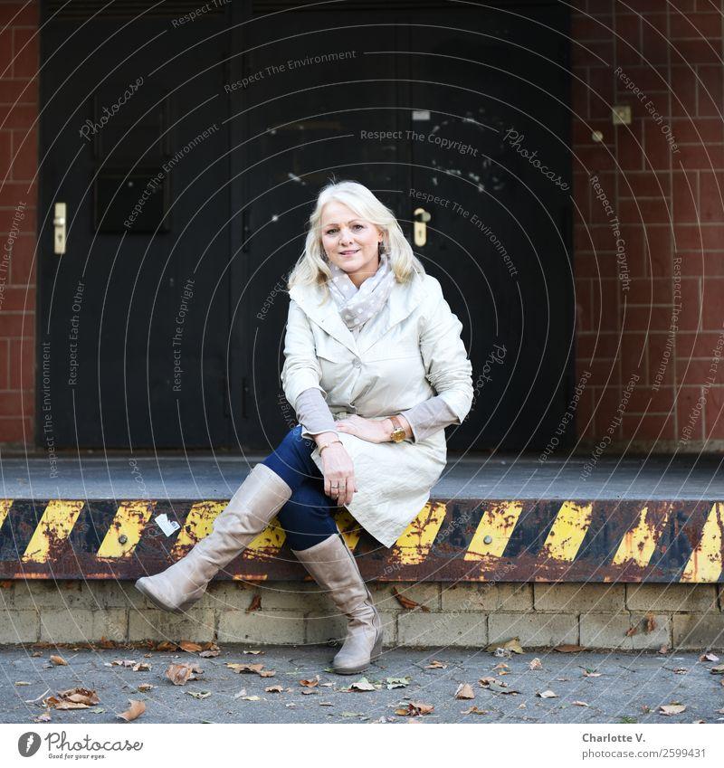 Kurze Rast Mensch feminin Frau Erwachsene Weiblicher Senior 1 45-60 Jahre Mauer Wand Tür Versand Eingang Mantel Stiefel blond langhaarig hocken Lächeln sitzen