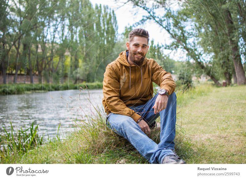 Lächelnder junger Mann, der am Flussufer sitzt. Lifestyle Leben Junger Mann Jugendliche 1 Mensch 18-30 Jahre Erwachsene Natur Herbst Schönes Wetter Gras