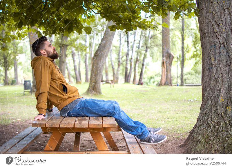 Mann sitzt in einem Park, auf einem Picknicktisch. Lifestyle Wellness Wohlgefühl Erholung Ferien & Urlaub & Reisen Freiheit Junger Mann Jugendliche Körper 1