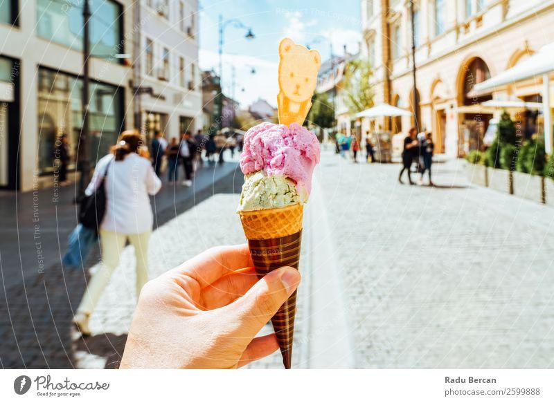 Mann hält grüne und rosa Eiscreme in der Hand. Lebensmittel Milcherzeugnisse Dessert Speiseeis Süßwaren Essen Fastfood Lifestyle Stil Freude