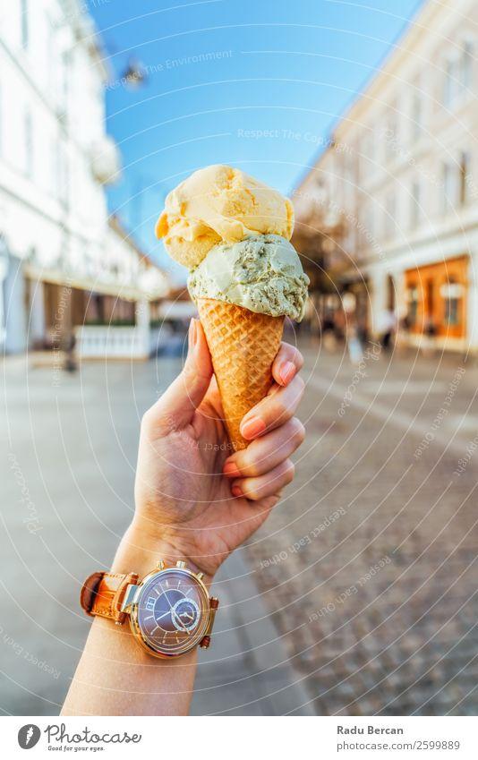 Frau hält grüne und gelbe Eiscreme in der Hand. Lebensmittel Milcherzeugnisse Dessert Speiseeis Süßwaren Essen Fastfood Lifestyle Stil Freude