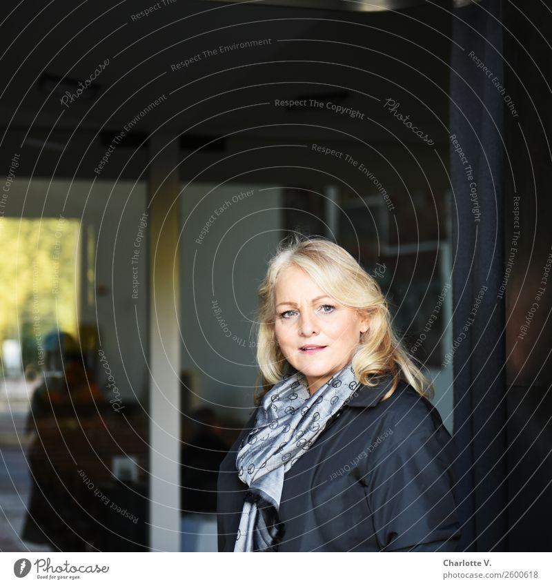 Komm mit! Mensch feminin Frau Erwachsene Weiblicher Senior 1 45-60 Jahre Fenster Eingang Schal blond langhaarig Glas Kommunizieren Lächeln leuchten Blick stehen