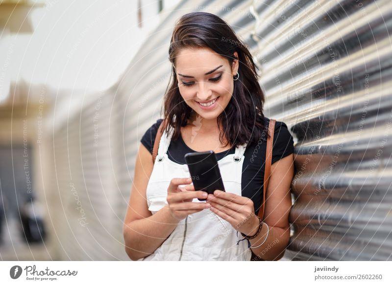 Lächelndes Mädchen, das mit ihrem Smartphone im Freien benutzt. Glück schön Haare & Frisuren Telefon PDA Technik & Technologie Mensch feminin Junge Frau