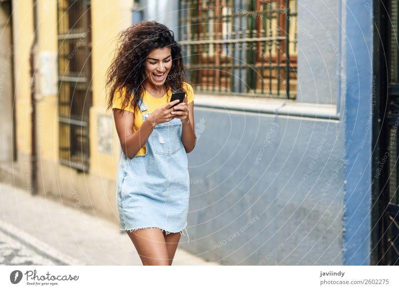 Afrikanische Frau, die auf der Straße geht und ihr Smartphone ansieht. Lifestyle Stil Glück schön Haare & Frisuren Telefon PDA Technik & Technologie Mensch