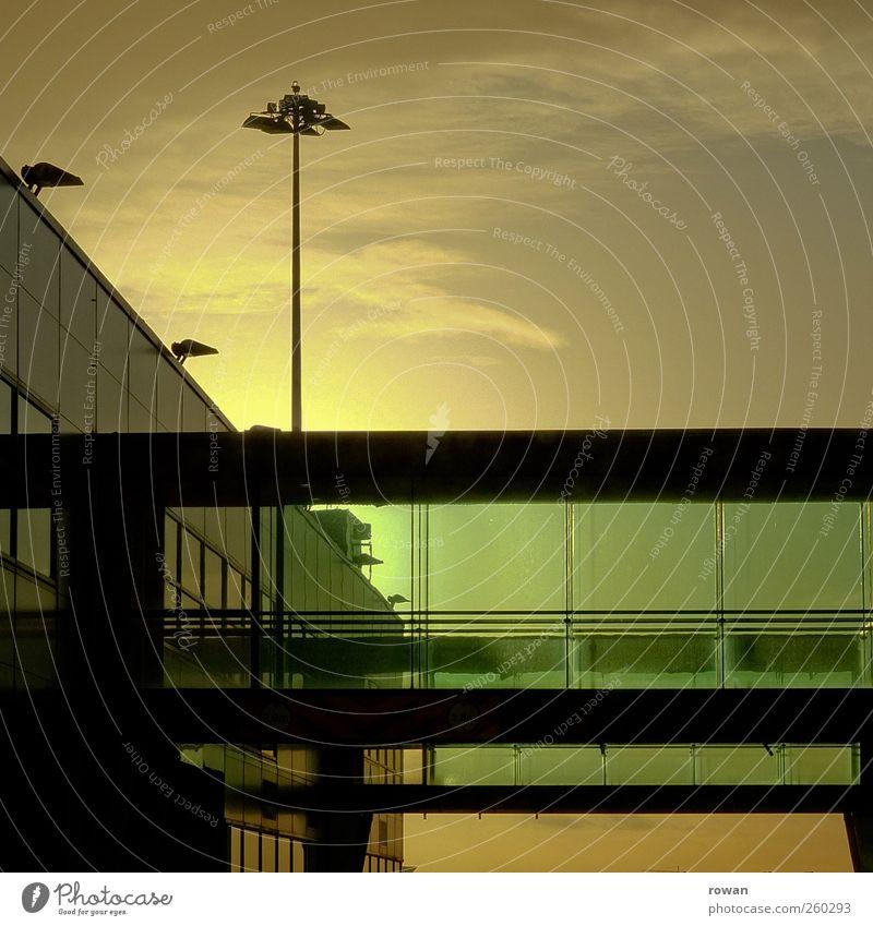 bruecke Bauwerk Gebäude Architektur Fassade Fenster ästhetisch modern kalt Glas Glasfassade grün Lampenständer Flughafen Sonnenuntergang Brücke Abend