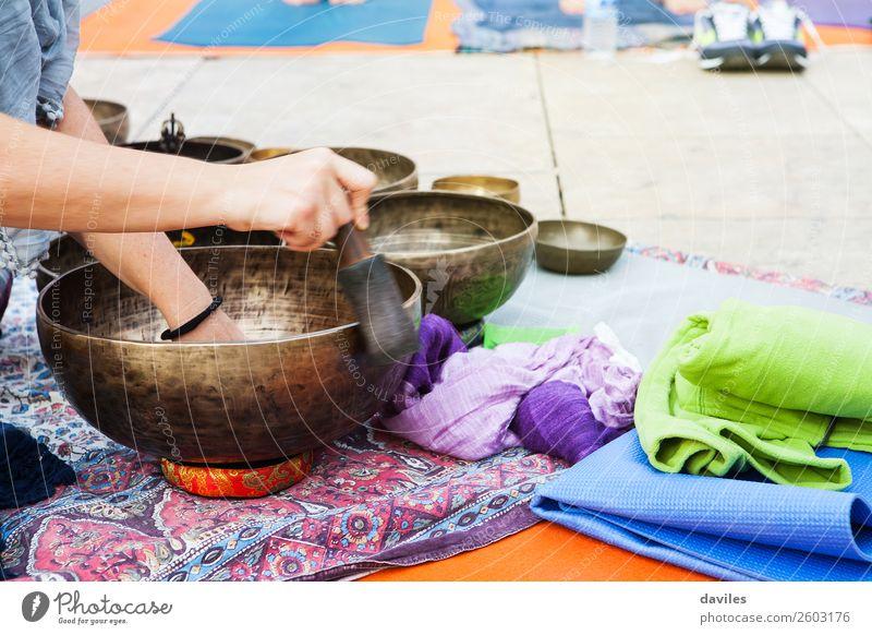 Hand spielt Yogaschalen im Freien. Lifestyle Wellness Erholung Meditation Spa Musik Mensch 1 Straße Metall Spielen Heilung Schüsseln Klang tibetisch Therapie