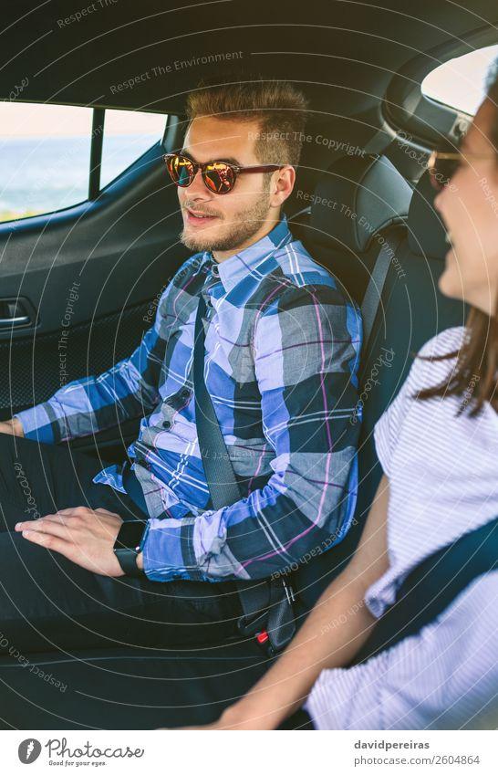 Junges Paar, das mit dem Auto unterwegs ist und Sicherheitsgurte anlegt. Lifestyle schön Freizeit & Hobby Ferien & Urlaub & Reisen Ausflug Mensch Frau