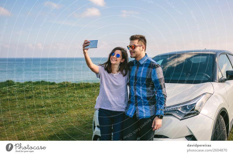 Junges Paar, das einen Selfie auf dem Auto macht. Lifestyle Freude Glück schön Ferien & Urlaub & Reisen Ausflug Meer PDA Mensch Frau Erwachsene Mann Gras Küste