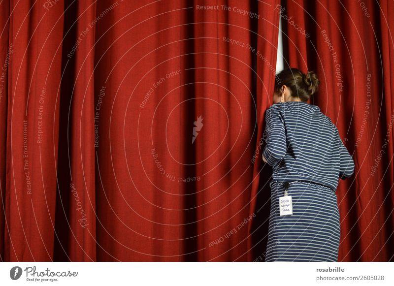 junge Frau in blauem Kleid wagt einen Blick hinter die Kulissen und schaut neugierig hinter einen roten Theatervorhang als Symbol für Hintergrundinfos, Einblicke oder Vorankündigungen