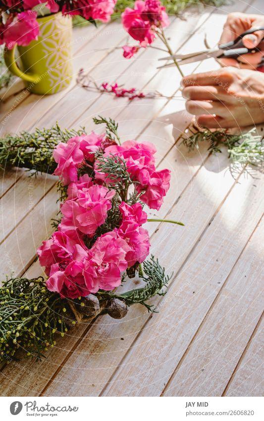 Florist bei der Arbeit: Erstellen eines Holzkranzes mit Zweigen aus Kiefernholz Dekoration & Verzierung Feste & Feiern Muttertag Erntedankfest