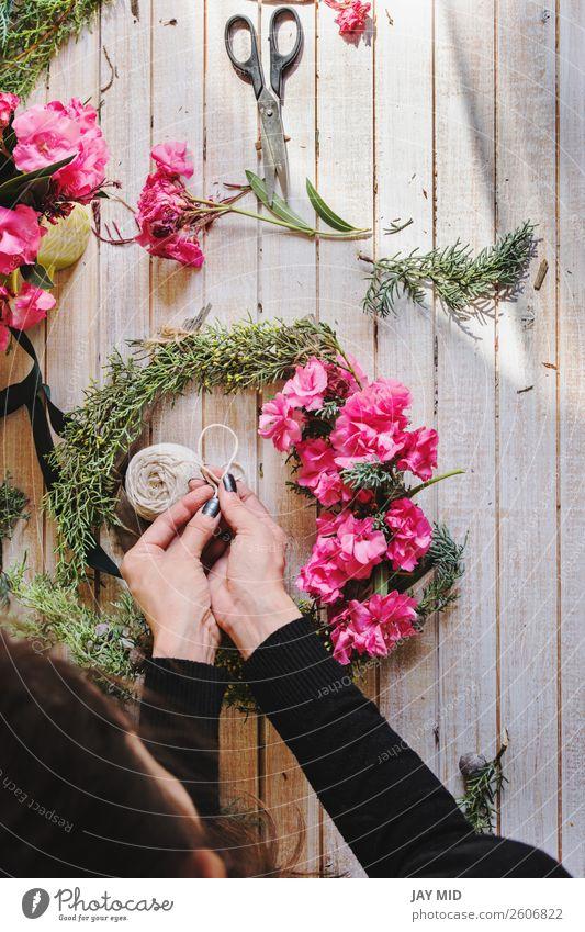 Florist bei der Arbeit Erstellung eines Holzkranzes mit rosa Blumen Dekoration & Verzierung Erntedankfest Weihnachten & Advent Silvester u. Neujahr