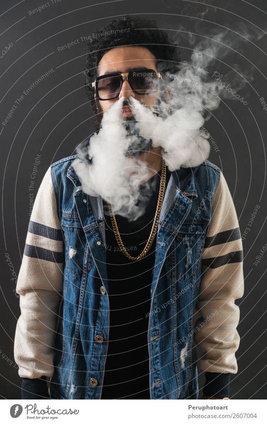 Junger Mann mit Sonnenbrille, der eine Wolke aus Rauch bläst. Lifestyle elegant Glück Technik & Technologie Mensch Erwachsene Wolken Vollbart schwarz Zigarette