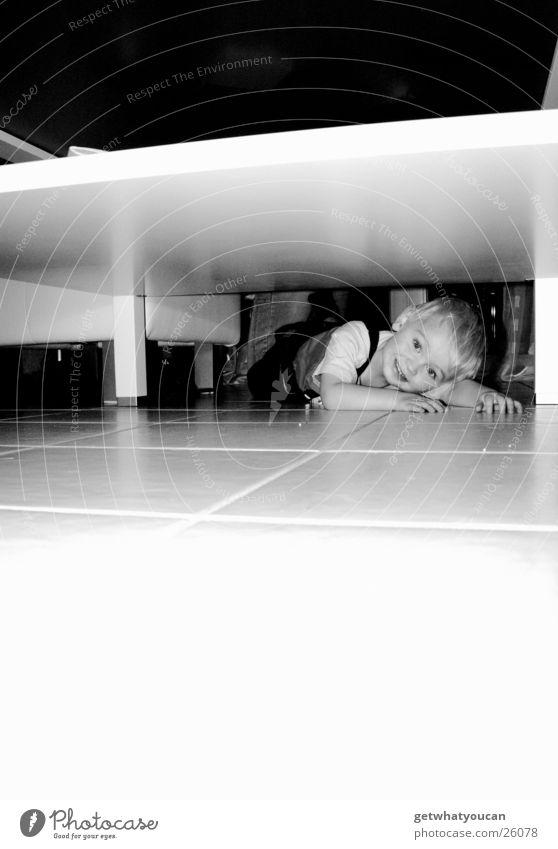 Unter Tage Kind Tisch weiß grell eng flach Suche finden Junge Bodenbelag Fliesen u. Kacheln hell Lampe verstecken liegen Blick Schwarzweißfoto Tischkante