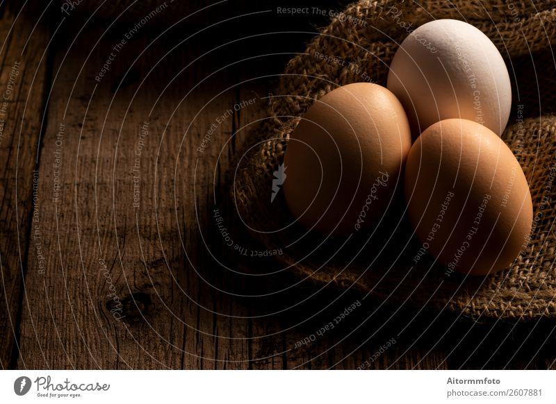 Frische Eier auf dunklem Holztisch Lebensmittel Ernährung Dekoration & Verzierung Tisch Ostern Natur Stoff frisch natürlich braun weiß Kreativität Tradition