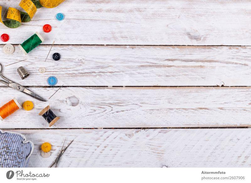 Set von verstreuten Nähzubehören auf weißem Holztisch Design schön Freizeit & Hobby Dekoration & Verzierung Tisch Handwerk Werkzeug Schere Stoff Accessoire