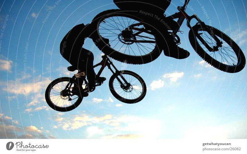 Rad am Kopp Fahrrad springen Trick Stunt Rampe Luft Gegenlicht Wolken schwarz Extremsport Mut Angst fliegen Street Fuß Himmel