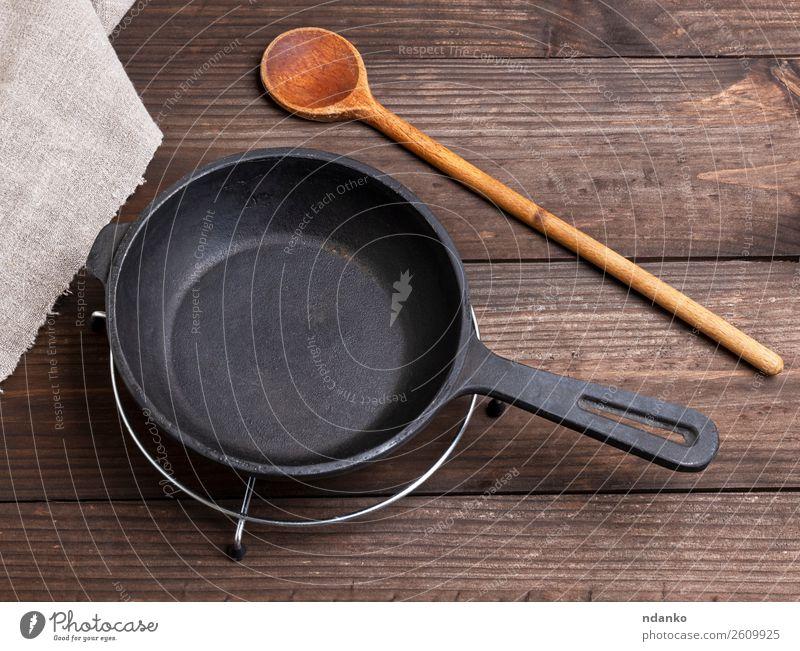 schwarze runde Gusspfanne aus Gusseisen Frühstück Abendessen Pfanne Löffel Küche Restaurant Metall Stahl stehen retro braun heimwärts leer Essen zubereiten