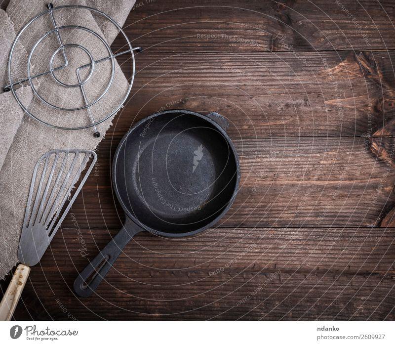 schwarze runde Gusspfanne aus Gusseisen Frühstück Abendessen Pfanne Besteck Küche Restaurant Werkzeug Metall Stahl stehen retro braun heimwärts leer