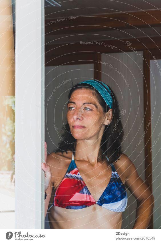 Frauenporträt, das sich auf eine Türseite lehnt und einen Badeanzug trägt. Lifestyle Freude Glück Freizeit & Hobby Ferien & Urlaub & Reisen Tourismus Sommer
