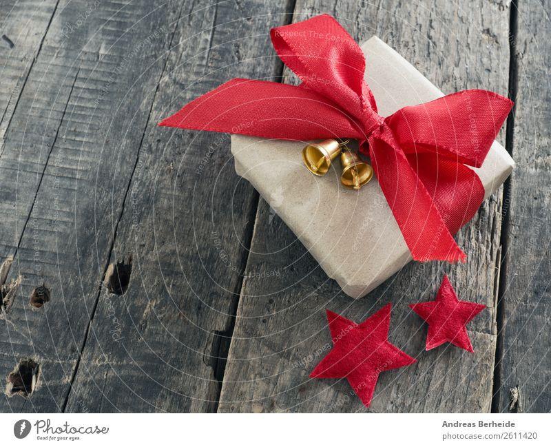 Ein Geschenk mit Schleifchen und Glöckchen Stil Winter Weihnachten & Advent Vorfreude Freude golden merry new nobody plank present red ribbon rustic season