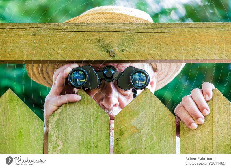 """ein Mann blickt mit einem Fernglas durch einen Zaun Mensch maskulin Erwachsene Männlicher Senior 1 """"Zaun Lattenzaun"""" Hut beobachten Neugier gereizt"""