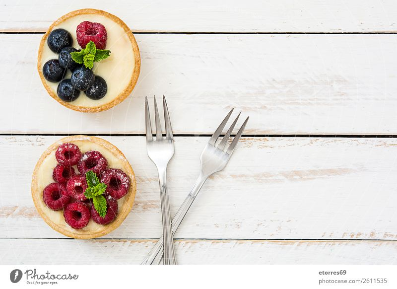 Köstliche Törtchen mit Himbeeren und Heidelbeeren Blaubeeren Frucht Dessert Lebensmittel Gesunde Ernährung Foodfotografie lecker Sahne Creme Vanillepudding